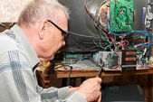 An elderly man repairing an old TV — Stock Photo