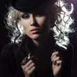 Portrait of a beautiful blonde girl in a hat. with an unusual ring on the fingerin contrasting light on a black background — Stock Photo