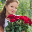 Beautiful woman of retirement age with a bouquet of red roses — Stock Photo