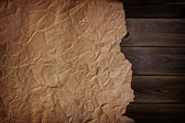 Old scorched paper on the wooden texture — Stock Photo