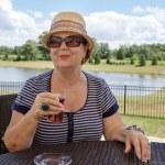 Senior woman enjoying a drink outdoors — Stock Photo