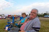 Elderly spectators sitting in deckchairs — Stock Photo