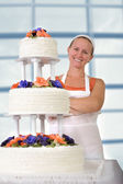 Happy Baker Lady smiling infront of her Ruffled Wedding Cake — Stock Photo