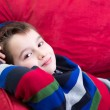 Young Boy on the Red Couch — Stock Photo