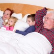 Grandparents Watching TV in the bed with their Grand kids — ストック写真