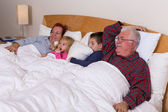 Grandparents Watching TV in the bed with their Grand kids — Φωτογραφία Αρχείου