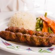 Adana Kebabs Served on a Lavash Bread Garnished with Vegetables — Stockfoto