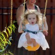 Toddler Girl on the Swing pushed by her Grandmother — Stock Photo #35501609