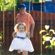 Toddler Girl on the Swing pushed by her Grandfather — Stock Photo