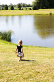 Little Toddler Girl Walking by the Pond Peacefully — Stock Photo