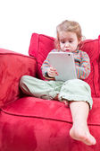 Cute little girl sitting on a sofa with a tablet — Stock Photo