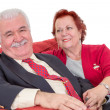 Devoted senior couple seated on a red sofa — Stock Photo #37950809