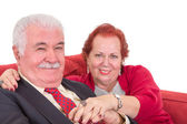 Affectionate senior couple on a red sofa — Stock fotografie