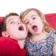 Two playful young children pulling faces — Stock Photo #37973663