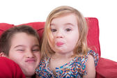 Young brother and sister pulling faces — Stock Photo