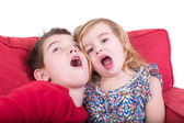 Two playful young children pulling faces — Stock Photo