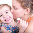Laughing little girl being kissed by her mother — Stock Photo
