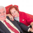 Senior couple sitting on a comfortable red couch — Stock Photo #38002195