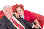 Senior couple sitting on a comfortable red couch — Stock Photo