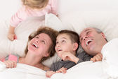 Playful little girl with her family in bed — Stock Photo