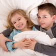 Mischievous young brother and sister in bed — Stock Photo