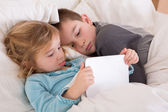 Cute little girl and boy reading a bedtime story — Stock Photo