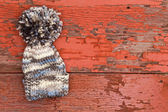 Cute warm woolen winter hat with a large pompom — Stock Photo