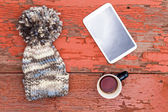 Cozy winter cap, tablet and tea on a grungy table — Stock Photo