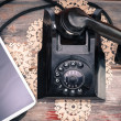 Tablet lying alongside a retro rotary telephone — Stock Photo