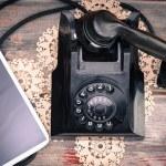 Tablet lying alongside a retro rotary telephone — Stock Photo