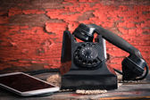 Old rotary telephone alongside a tablet computer — Stock Photo