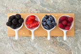 Assorted fresh berries in taster dishes — Stock Photo