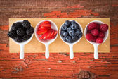 Fresh assorted berries on a grungy wooden counter — Stock Photo