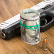 Handgun with a roll of dollar bills and a bullet — Stock Photo #42209367