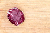 Red radicchio on a bamboo board — Stock Photo
