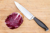 Red radicchio with a kitchen knife — Stock Photo