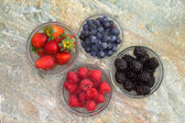 Selection of different fresh berries in glass jars — Stock Photo
