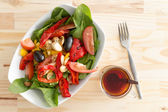 Baby spinach salad with olives, peppers and tomato — Stock Photo