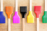 Row of kitchen brushes with colorful bristles — Stock Photo