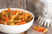 Multicoloured spinach and tomato fusilli pasta — Stock Photo