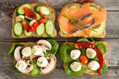 Four delicious open sandwiches on a picnic table — Stock Photo