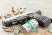 Handgun with money and scattered bullets — Stock Photo