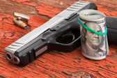Gun with a roll of 100 dollar banknotes — Stock Photo