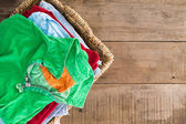 Clean unironed summer clothes in a laundry basket — Stock Photo