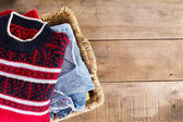 Wicker basket with clean fresh winter clothes — Stock Photo
