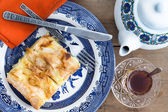 Slice of Turkish borek served with a cup of tea — Stock Photo