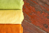 Fresh clean green, yellow and orange towels — Stock Photo