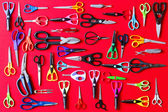 Display of multiple scissors on red — Stock Photo
