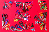 Random groups of multiple scissors conceptualy laid on red — Stock Photo