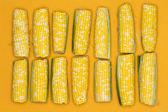 świeże corncobs w kolejce na żółtym tle — Zdjęcie stockowe